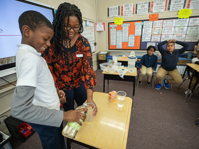 Barack Obama Magnet School fourth-grader Warren Meeks, 10, pours vinegar for a classroom demonstration led by SGSHS student Adesuwa Ekunwe. Ekunwe taught a lesson on light for Project REACH, a collaboration between UMMC and Obama Magnet to enhance science education.