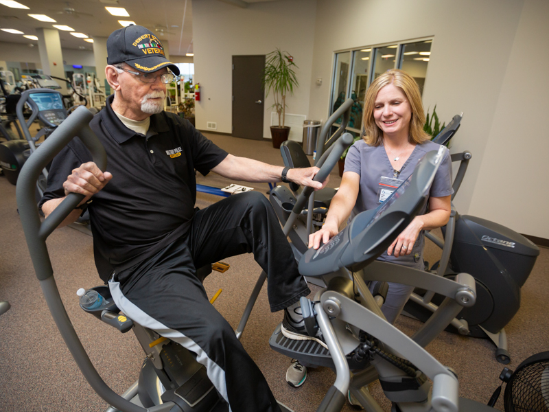 Richard Norton of Florence exercises on a seated elliptical with guidance from physical therapist Rachel Dear.