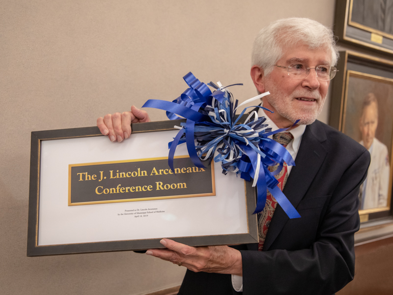 Dr. Lincoln Arceneaux accepts a framed representation of the plaque marking the room named for him.
