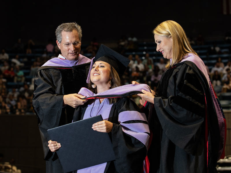 Dr. Alan Lucas, left, and his wife, Dr. Melinda Lucas, hood their daughter, Meredith Lucas, as she receives the Doctor of Dental Medicine. Her parents are alumni of the School of Dentistry.