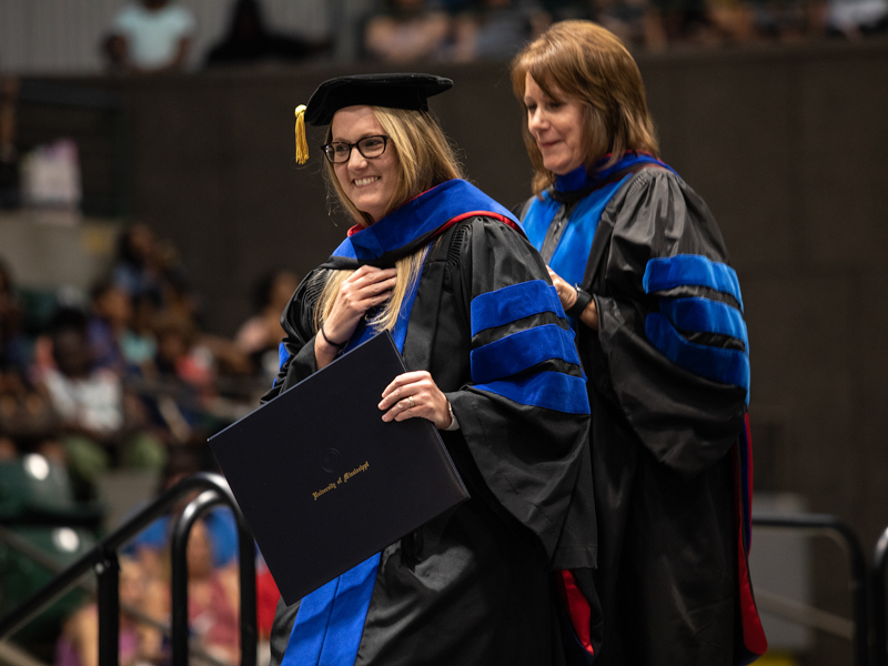 After receiving her Ph.D. in Nursing, Katie Hall, left, is hooded by Dr. Jennifer Robinson, one of her professors.