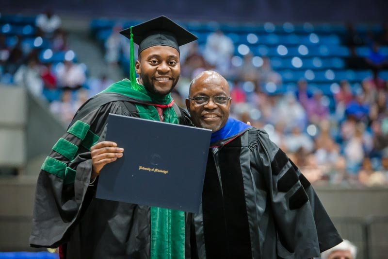 School of Medicine graduate Dr. Sosa Adah received his hood from his father, Dr. Felix Adah, professor of physical therapy in the School of Health Related Professions.