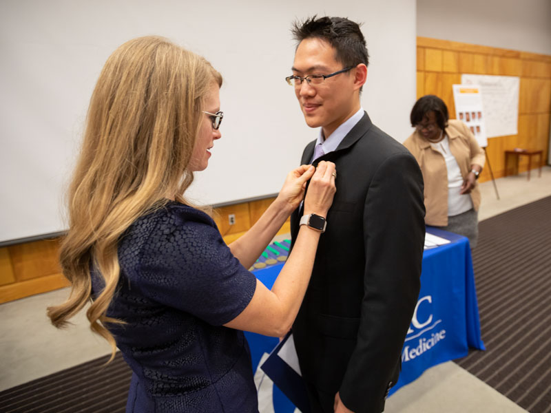 Dr. Lyssa Weatherly, the Gold Humanism chapter's faculty advisor, presents a lapel pin to Dr. Michael Yeung-Lai-Wah, a family medicine resident.