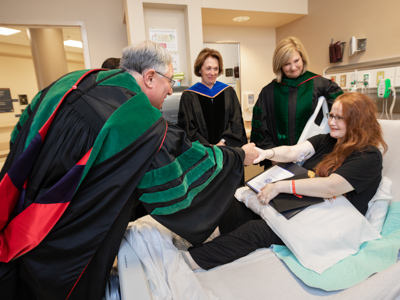 Dr. Ralph Didlake congratulates Sarah Herrington during her bedside graduation ceremony that included Dr. Jessica Bailey, Dr. LouAnn Woodward and (not pictured) Dr. Kristi Moore.