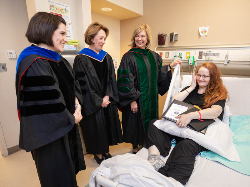 Sarah Herrington is overwhelmed by the kindness of those who brought graduation to her hospital room, including Dr. Kristi Moore, left, Dr. Jessica Bailey, second from left, and Dr. LouAnn Woodward.