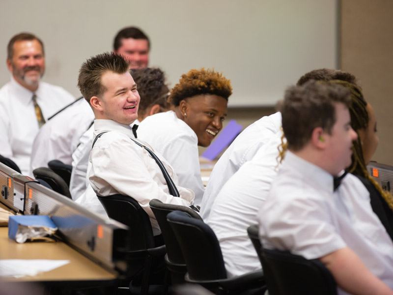 Project SEARCH participants, including Taton Wetzel, center left, and Joshua Wilson, center right, laugh during their program graduation ceremony May 17.
