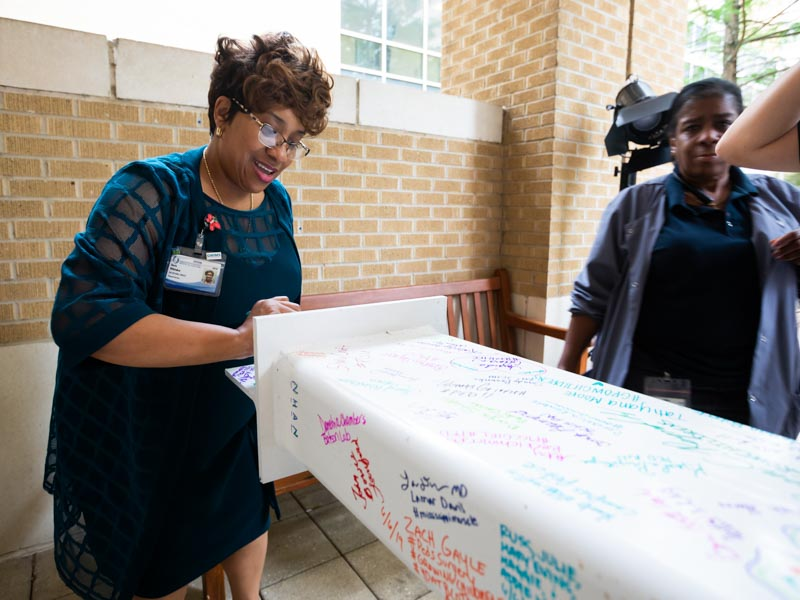 Doris Whitaker, left, director of Pastoral Services at UMMC, signs her name to the beam.