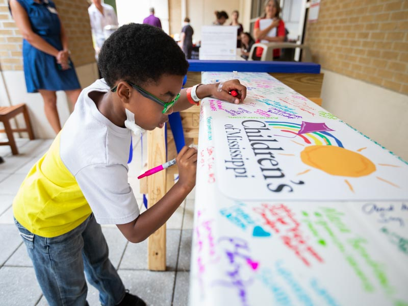 Batson patient Tayden Franklin of Meridian signs the beam during Thursday's signing party in the Rainbow Garden.