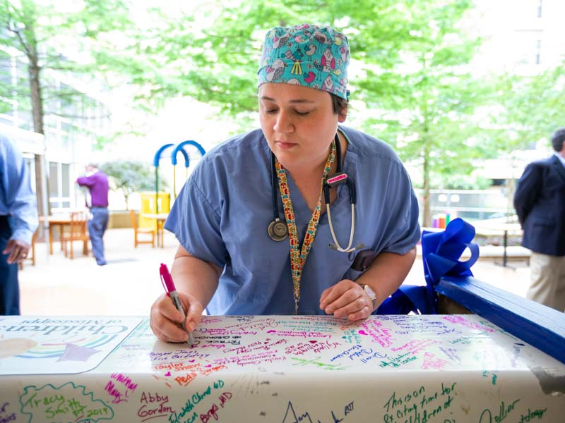 Pediatric Anesthesiologist Sara Robertson signs the beam at the Rainbow Garden signing party June 6.