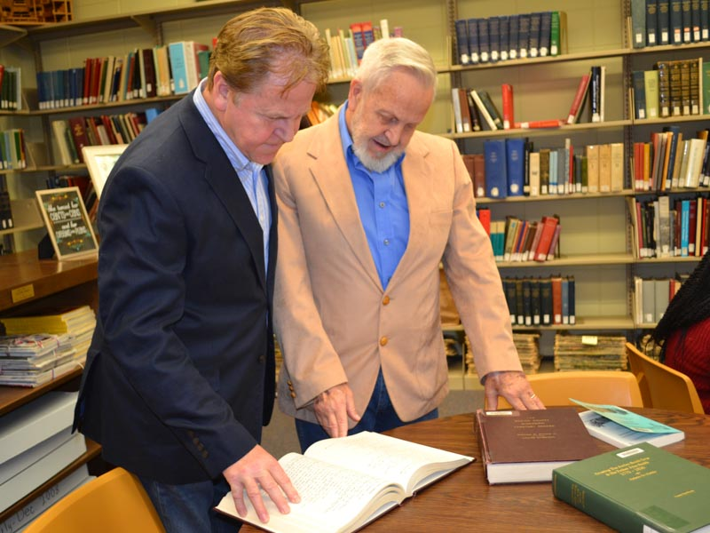 During a recent visit to the Medical Center, Wayne Lee, left, and James Lee examine historical documents related to the asylum that had housed their grandfather, John Benedict Whitfill.