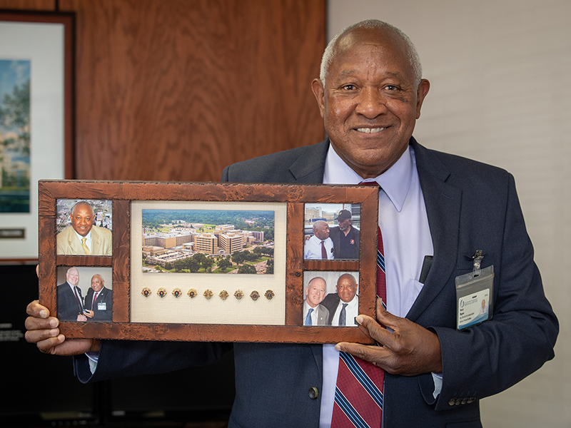 Mr. Ivory Bogan holding a photo frame displaying his many years of service pins