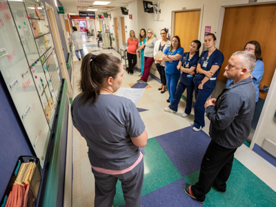 Registered nurse Anna Odom, left, leads a morning huddle on 2 Children's as nurse manager Wesley Smith, right, and other floor staff look on.