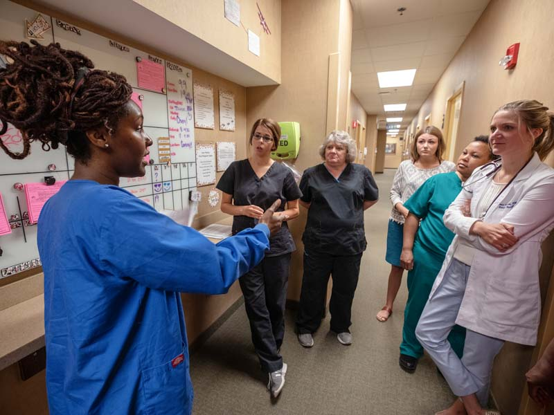 Huddling around Family Medicine's visual management board are, from left, Sondra Green, Alicia Hall, Cathy Kirkpatrick, Reagan Rayborn, Connye Henry and Lyndsey Carlton.