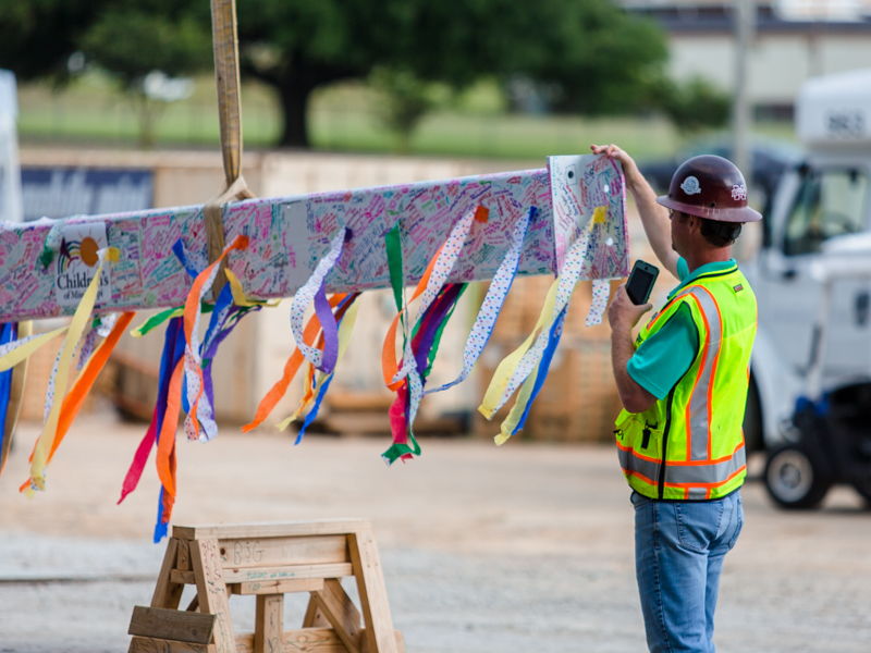 A beam covered with streamers and signatures is prepared for being lifted to the top of UMMC's seven-story pediatric expansion.