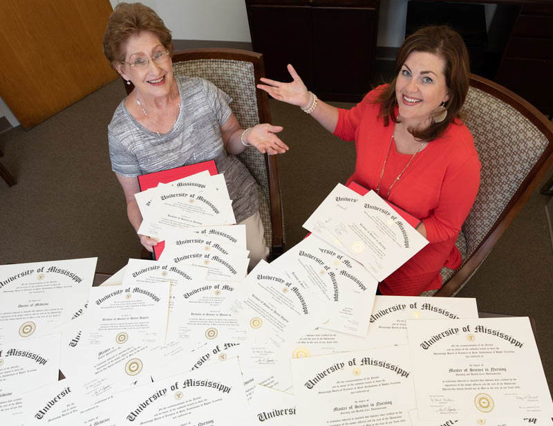 For UMMC's former registrar Barbara Westerfield, left, and current registrar Emily Cole, it seems there's no end to the diplomas being readied for handout during Commencement season at UMMC – and that's a good thing!