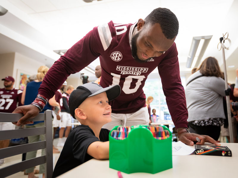 Mississippi State linebacker Leo Lewis watches as patient Lane Smith of Waynesboro colors during an afternoon play session at the state's only children's hospital.
