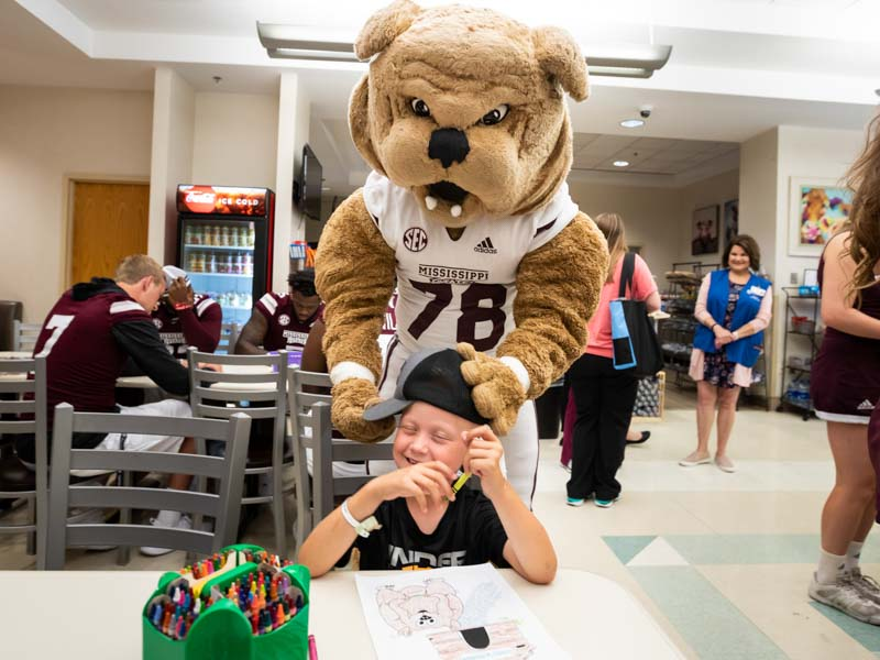 Mississippi State mascot Bully adjusts the cap of patient Lane Smith of Waynesboro.