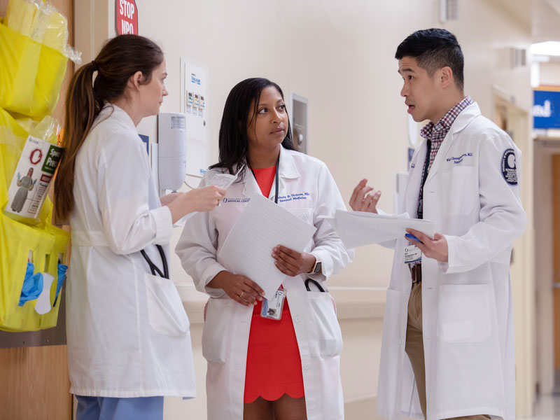 Dr. Malorie Holmes, center, conducts rounds with Dr. Alisha Parker, left, a nephrology fellow, and Dr. Wisit Cheungpasitporn, right, assistant professor of medicine, nephrology.