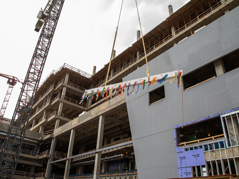 The ceremonial construction beam, decked with streamers, rises toward the top of UMMC's seven-story pediatric expansion.