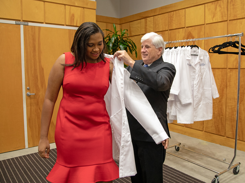 Ashley Griffin of Greenwood receives her lab coat from Dr. Joey Granger at School of Graduate Studies in the Health Sciences' first White Coat Ceremony.