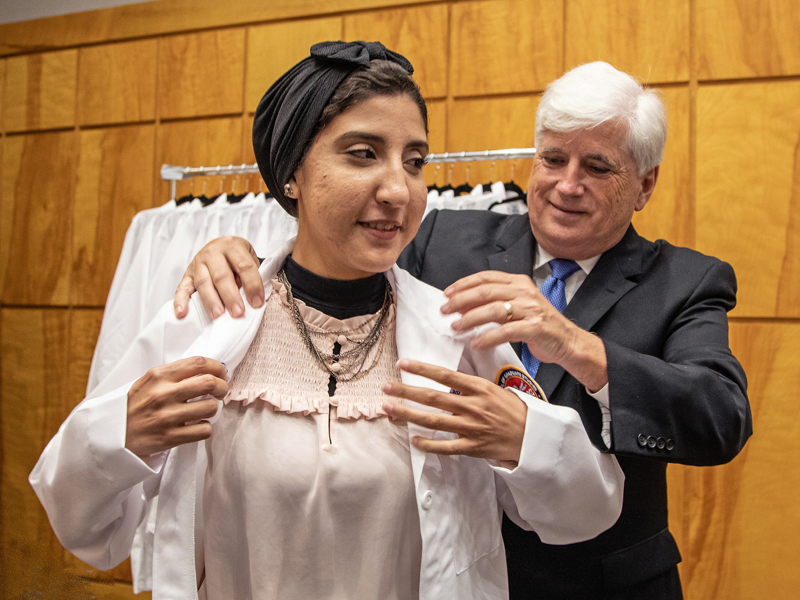 Aya Ali, an incoming Ph.D. student, receives her lab coat from Dr. Joey Granger, SGSHS dean, during the school's white coat ceremony.