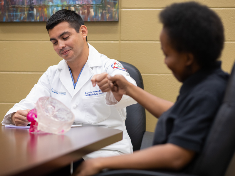 Dr. Ignacio Velasco Martinez and patient Violet Thompson share a fist bump.