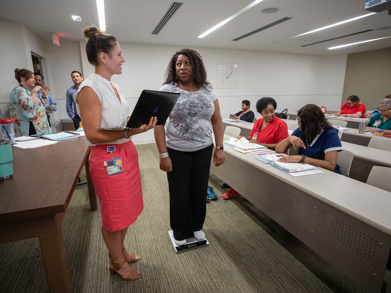 Dr. Abigail Gamble, left, assistant professor of preventive medicine, weighs in Pam Greenwood. a Human Resources service partner, during a diabetes prevention class.