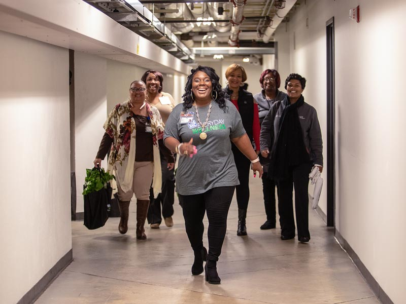 Makeba Harris, center, a billing specialist and wellness champion, walks coworkers through a tunnel at the Clinton Billing Office.