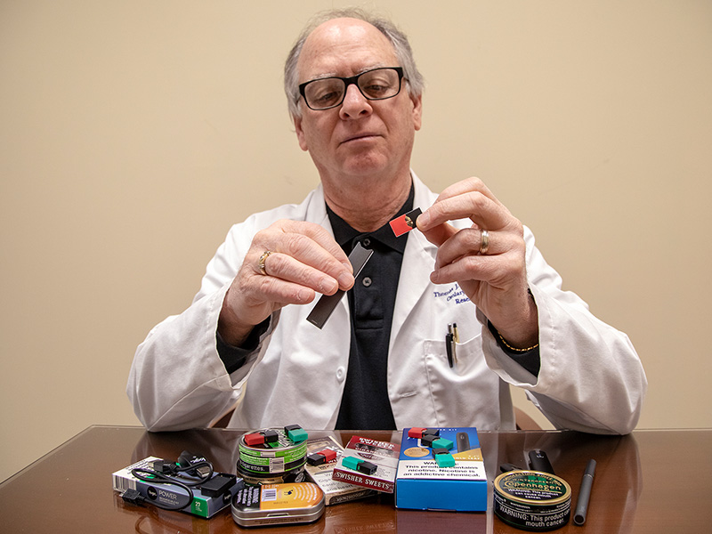 Dr. Thomas Payne, professor of otolaryngology and communicative sciences and director of the ACT Center for Tobacco Treatment, Education and Research, explains how an e-cigarette in the shape of a flash drive is used.
