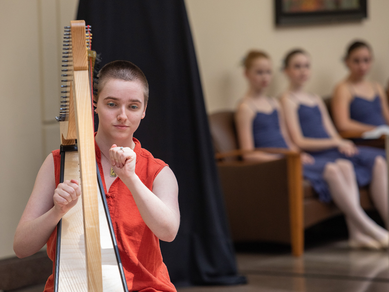 Harpist/vocalist Laura Pitts performs one of three musical selections as dancers from Ballet Mississippi wait in the wings.