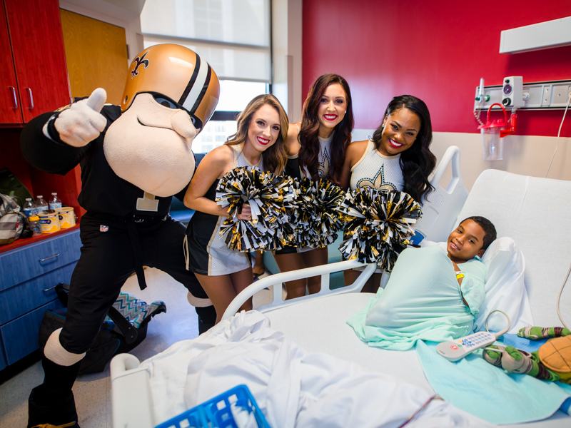 Children's of Mississippi patient Johnny Roper of D'Iberville gets a surprise visit from Sir Saint and Saintsations Kassidi, Rachel, and Kianna.