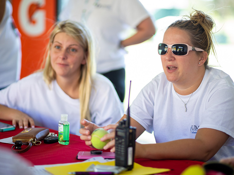 Ashley Breeland, right, a student in the masters of health care administration program, shares about volunteering at the first aid tent as Chelsea Pickle, left, of the RN to BSN program, listens.