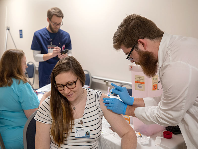 Anna Barnes, left, physical therapist, is armed against the flu with a vaccination from Austin Fitts, third-year pharmacy student.