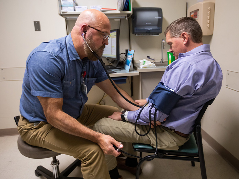 TEAM Clinic nurse practitioner Jim Miller, left, takes the blood pressure of patient Wes McComas.