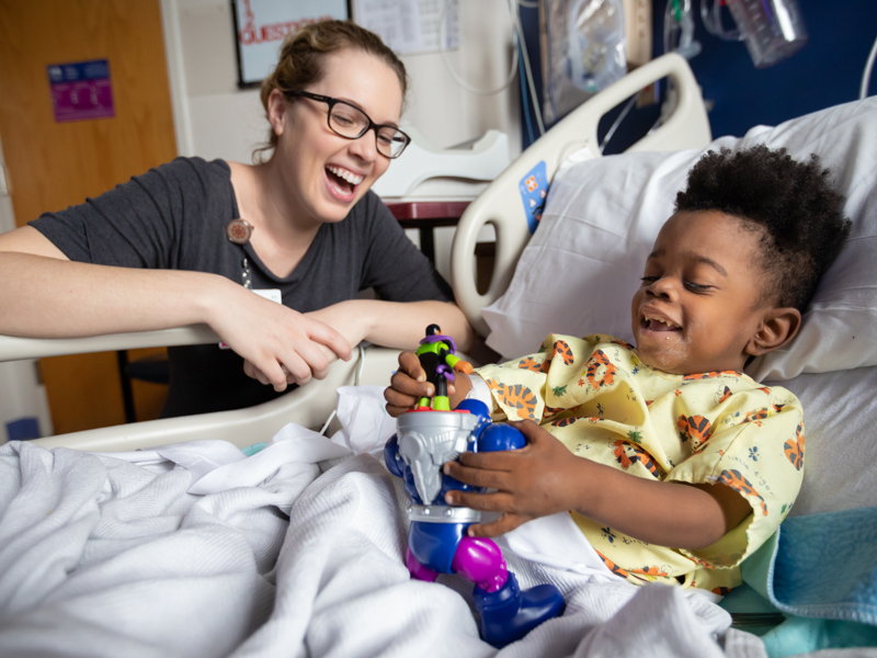 Madeline Wilson, Children's of Mississippi Child Life specialist, laughs with Keidron Hall of Gulfport during his hospital stay.