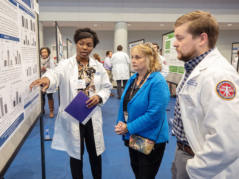 Dr. Barbara Alexander, center, 2019 School of Graduate Studies in the Health Sciences Distinguished Alumna, talks to Ph.D. students Olivia Travis and Corbin Shields during SGSHS Research Day.