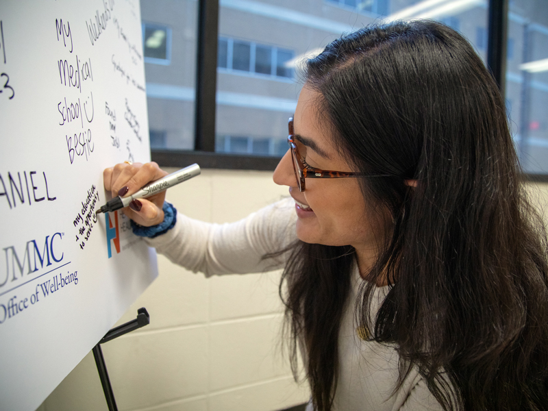 Ruhi Randhawa, a School of Medicine student, writes that she's grateful for her education and the opportunity to serve on a poster near classroom R153. The poster is sponsored by several UMMC groups, including the Office of Well-being.