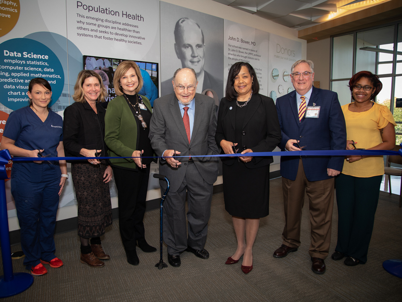 Cutting the ribbon during the John D. Bower School of Population Health's open house include, from left, Dawn McLendon, SOPH student; Anne Travis, Bower Foundation CEO; Dr. LouAnn Woodward, UMMC vice chancellor for health affairs; Dr. John Bower, professor emeritus of medicine and first leader of the Bower Foundation; Dr. Bettina Beech, founding dean of the SOPH; Dr. Ralph Didlake, UMMC associate vice chancellor for academic affairs; and Courtney Gomilia, SOPH student.