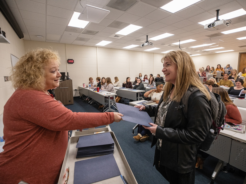 Rhonda Donald, education administrator in the School of Nursing, hands information to incoming student Teresa Moncrief.
