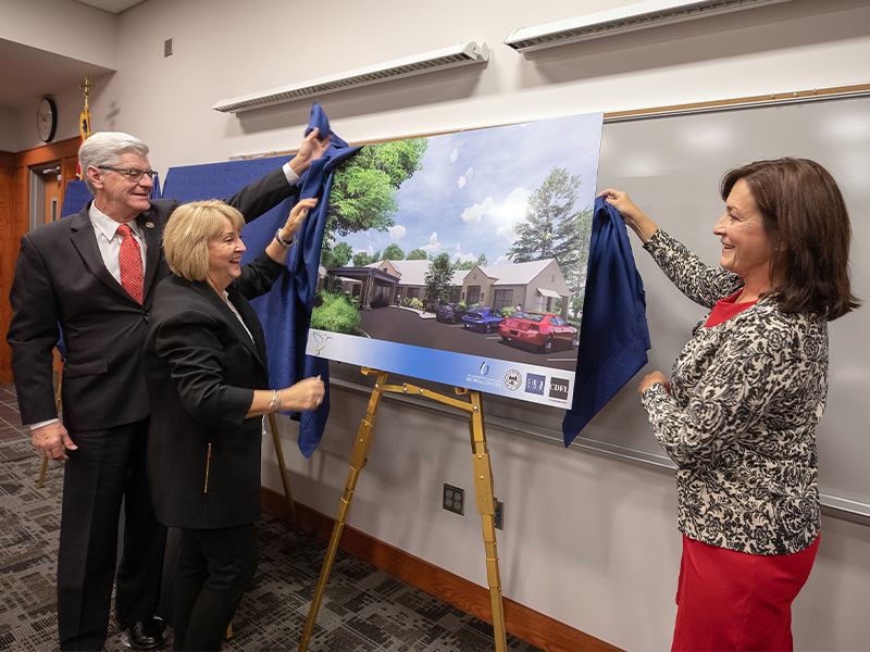 Gov. Phil Bryant looks on as wife Deborah Bryant and Dr. Mary Taylor, right, unveil a rendering of the state's first pediatric skilled nursing facility.