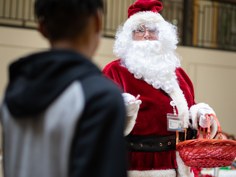 Santa Claus hands out candy canes to passers by inside the adult hospital atrium.