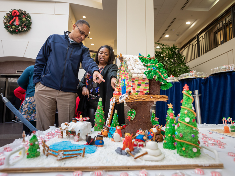 Donor heart recipient Timothy Lewis, left, and Patrice Donald, magnet program manager in the Office of Nursing Quality and Development, check out Nursing Quality's entry into UMMC's annual gingerbread house competition. Nursing Quality's entry took second place.