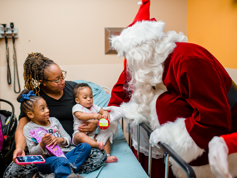 Santa gives Zaharia Primer of Jackson and her sister, Amelia, leftt, toys during his annual stop at Children's of Mississippi.