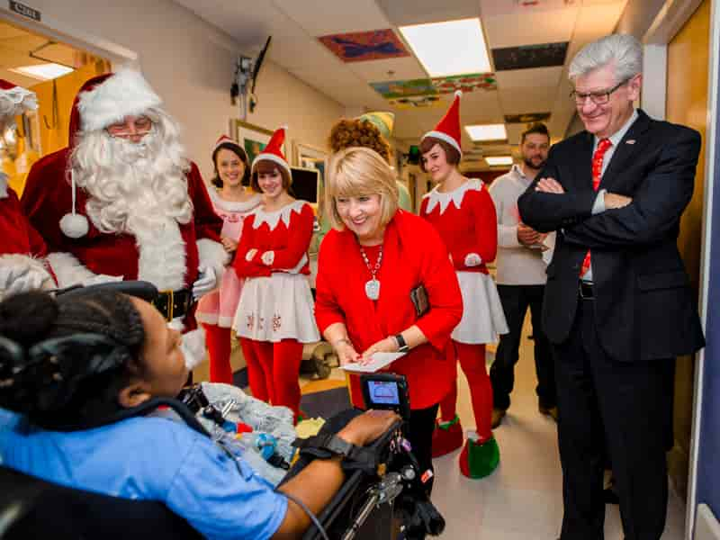 Gov. Phil Bryant, right, and First Lady Deborah Bryant, center, along with Santa, Mrs. Claus and a team of elves, visit with Children's of Mississippi patient DeAsia Scott.