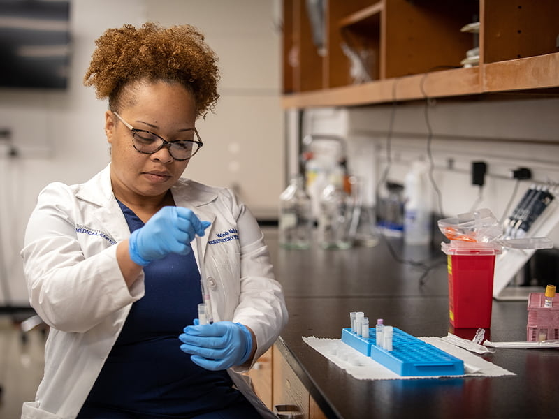 Malinda McBride, biorepository specialist III, draws a sample in the Biobank's laboratory.