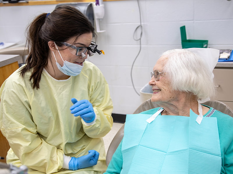 Taylor Campbell, left, third-year dental student, visits with Imogene Clark, who has been a School of Dentistry patient since 1978.