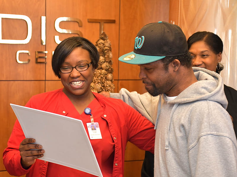As part of Michael Jordan's festive send-off, Methodist Specialty Care Center Activities Director Courtney Jones presented him with a card signed by staff and other residents. Photo by Carey Miller/Methodist Rehabilitation Center