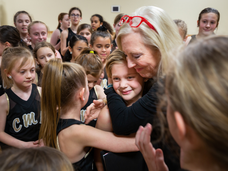 Surrounded by fellow dancers, Sybil gets a hug from her dance teacher, Carol Merrill.