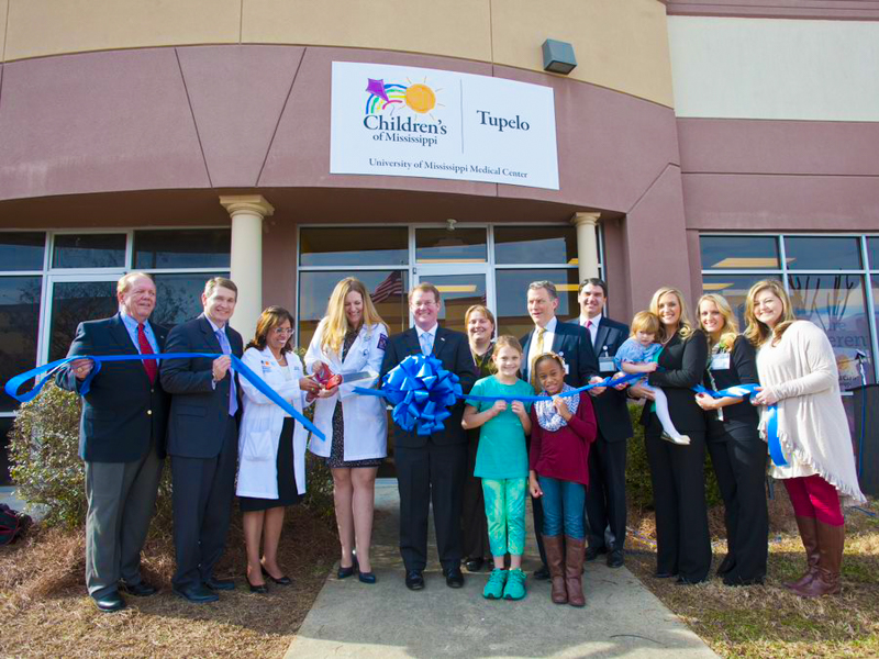 A group of people cuts the ribbon in front of the Children's of Mississippi Tupelo Clinic.