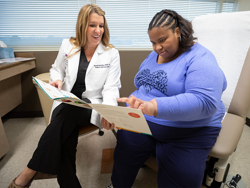 Nurse practitioner holds open a meal choice pamphlet to a patient while the patient points.